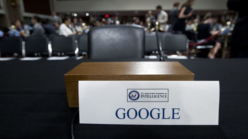 FILE- In this Sept. 5, 2018, file photo an empty chair reserved for Google's parent Alphabet, which