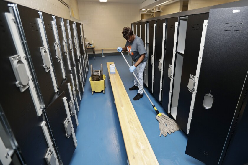 Custodian Joan Garner washes the floor in the pool locker room at Orange High School in Pepper Pike, Ohio.