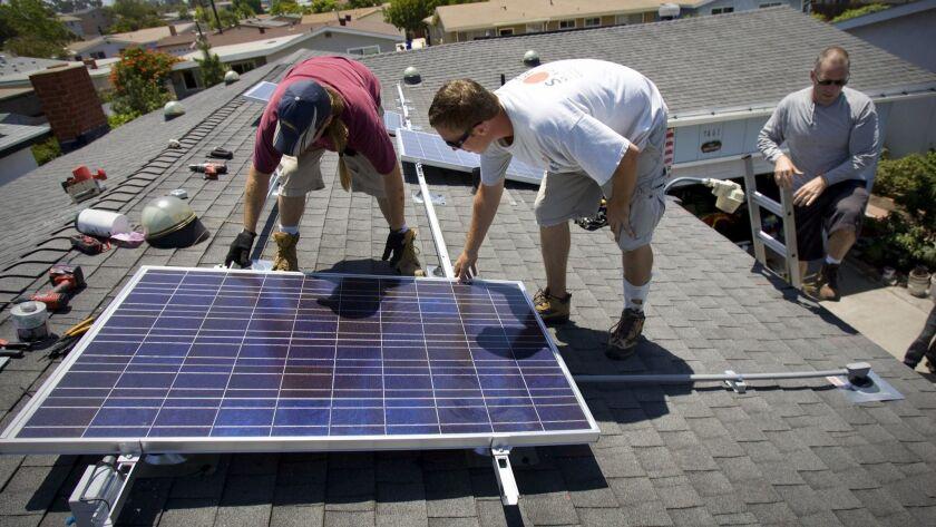 JULY 15, 2009, SAN DIEGO, CALIFORNIA, USA ................ Installer Jason Ingram (left) installs