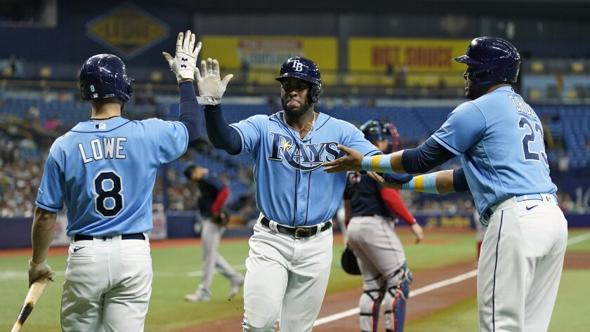 Tampa Bay Rays' Yandy Diaz, center, celebrates with Nelson Cruz, right, and Brandon Lowe, left, after scoring on a two-run double by Wander Franco off Boston Red Sox starting pitcher Martin Perez during the third inning of a baseball game Friday, July 30, 2021, in St. Petersburg, Fla. (AP Photo/Chris O'Meara)