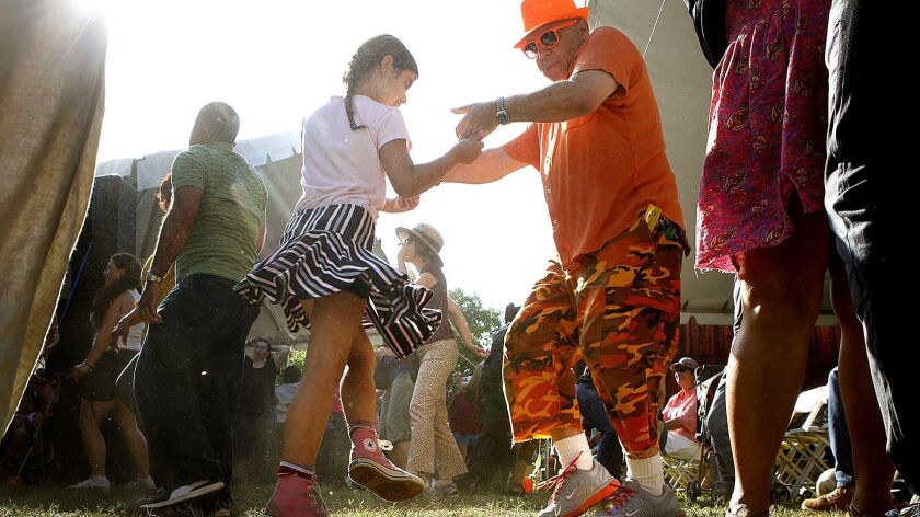 LOS ANGELES-CA-JUNE 2, 2013: Joy Mitchell, 9, and her father Nigel, center, dance to live music amon