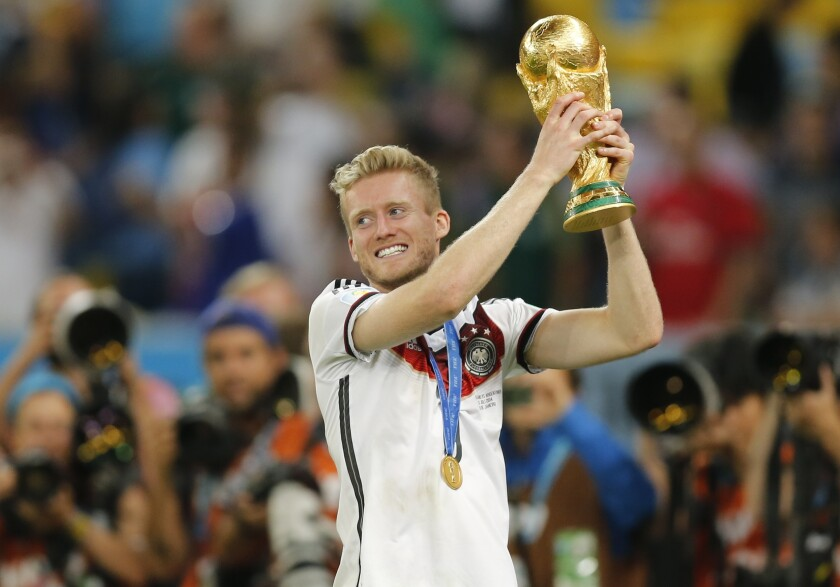Germany's Andre Schuerrle lifts the trophy after the World Cup final soccer match between Germany and Argentina at the Maracana Stadium in Rio de Janeiro, Brazil, Sunday, July 13, 2014. Former Germany forward André Schürrle has retired aged just 29 after failing to recapture the form that helped him star for Bayer Leverkusen and Chelsea and win the World Cup in 2014. (AP Photo/Frank Augstein)