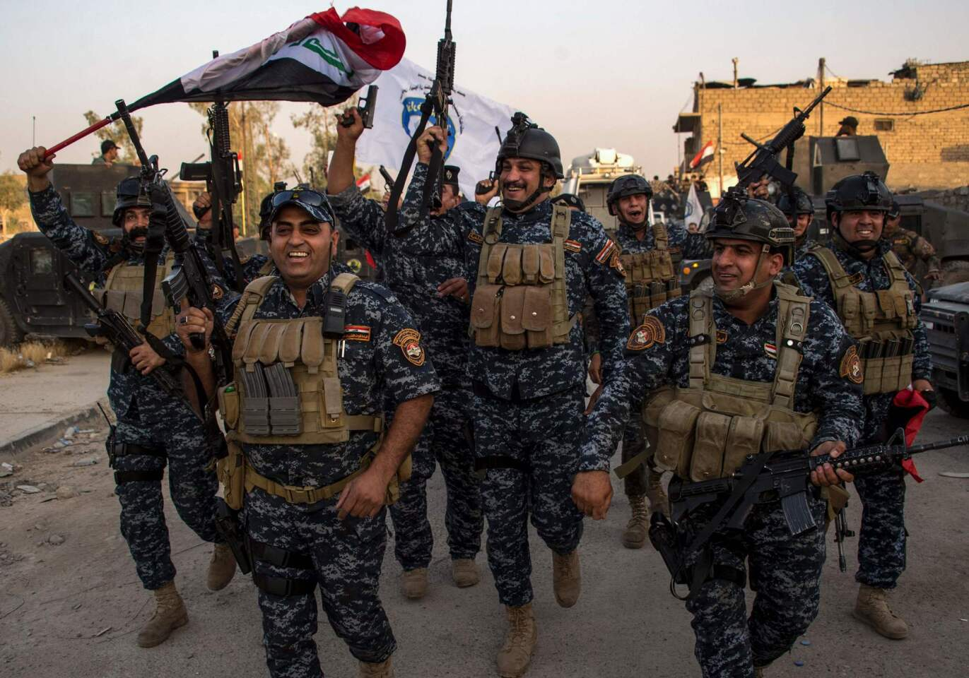 """Members of the Iraqi federal police forces celebrate in the Old City of Mosul on July 10, 2017, after the government's announcement of the """"liberation"""" of the embattled city from Islamic State fighters."""