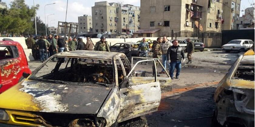 En esta fotografía difundida por la agencia de noticias oficial siria, SANA, soldados y policías no uniformados se reúnen en el lugar de una explosión que al menos a 10 personas e hirió a otras en la capital siria Damasco. El grupo Estado Islámico se atribuyó el ataque suicida que causó mucho daño material a edificios y autos en la zona. El grupo EI juró perpetrar más ataques en el futuro. (SANA vía AP)