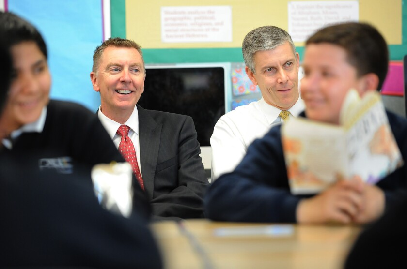 Former L.A. Unified schools Supt. John Deasy, left, and U.S. Secretary of Education Arne Duncan listen to a reading class at Dr. Julian Nava Learning Academy in Los Angeles in 2014. Duncan is stepping down from his post in December.