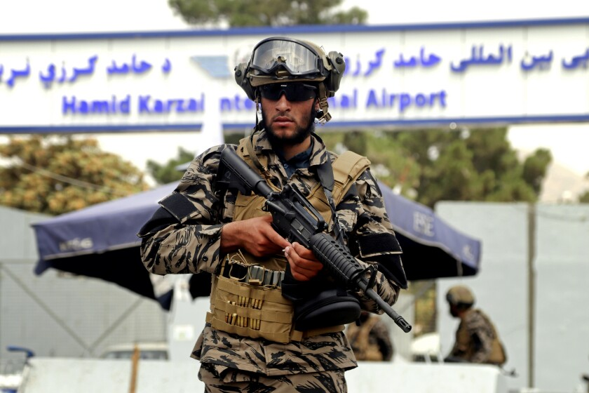 A Taliban fighter stands guard outside Kabul airport.