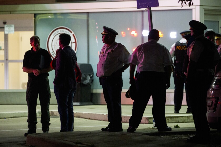 Police gather outside Stroger Hospital where two officers were brought after being shot while dispersing a crowd on the 100 block of North Long Avenue during the Fourth of July holiday weekend in the early hours of Monday, July 5, 2021, in Chicago. (Armando L. Sanchez/Chicago Tribune via AP)