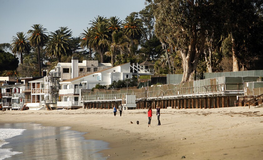 People walk along the beach in Montecito last week near the shuttered Miramar hotel site. The Montecito Planning Commission on Wednesday gave L.A. shopping mall developer Rick Caruso approval to build a 170-room, cottage-style luxury resort on the site 100 miles northwest of Los Angeles.