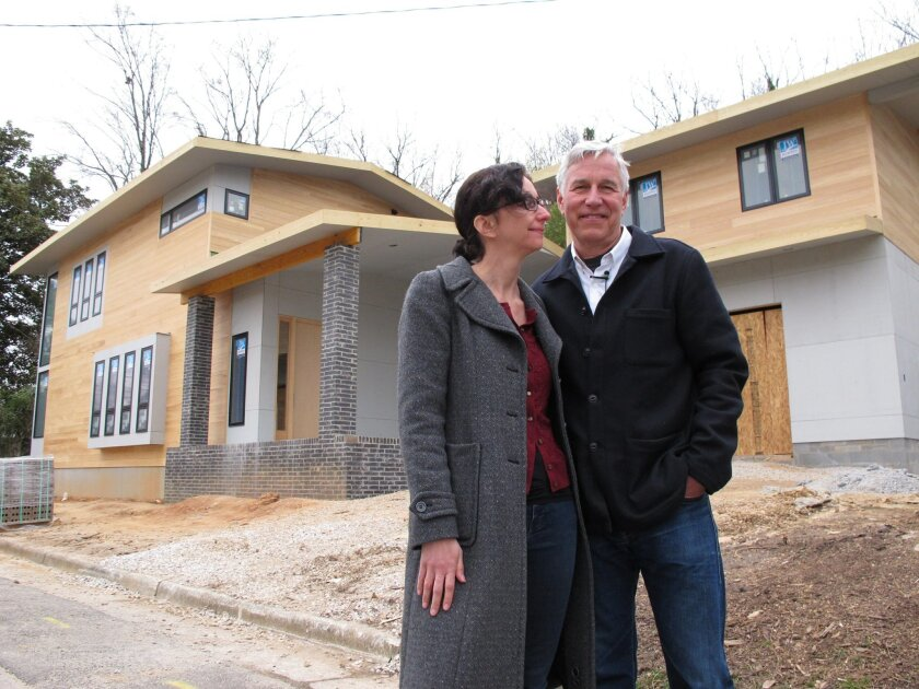 FILE- In this March 16, 2014, file photo, Architect Louis Cherry and his wife, Marsha Gordon, stand in front of their new home in the Historic Oakwood neighborhood of Raleigh, N.C. The couple who has fought for years to build a modern house in a historic Southern neighborhood won the latest round i