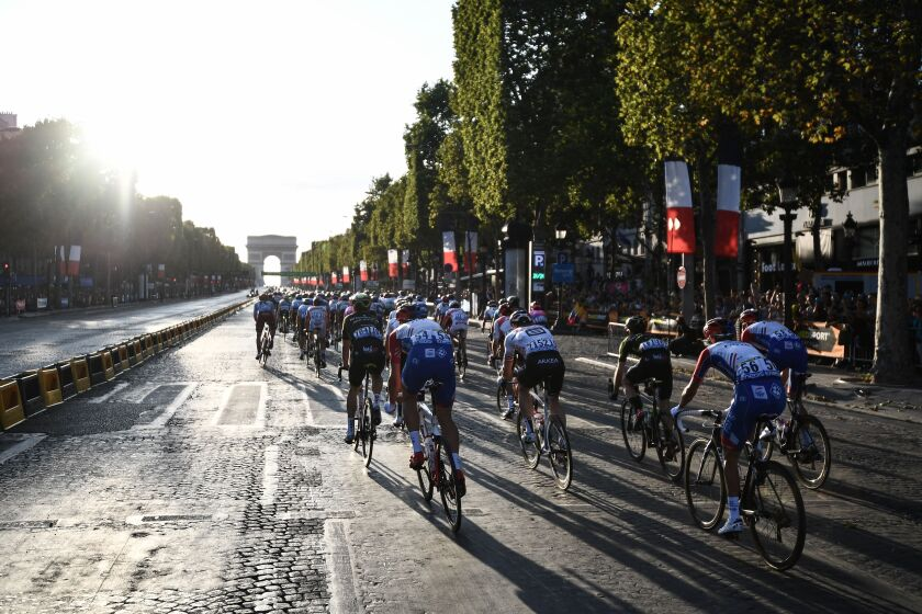 Cyclists ride down the Champs Elysees in Paris with the Arc de Triomphe ahead of them.