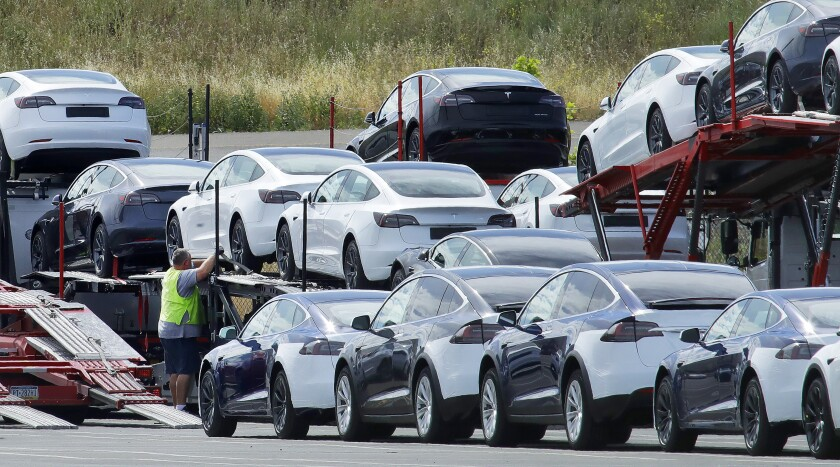 Teslas are loaded onto carriers at the company's plant in Fremont.
