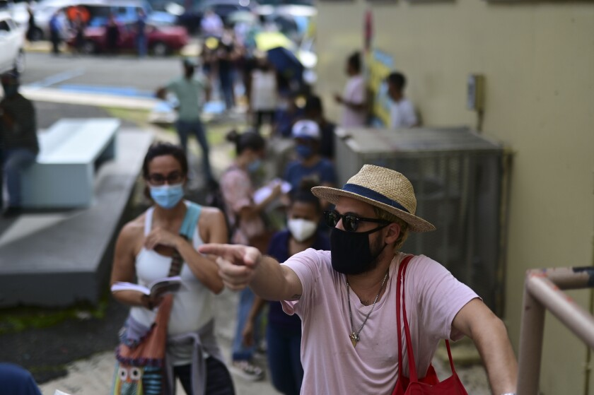 People wearing masks amid the COVID-19 pandemic wait in line to vote in the general election at a polling center set up at the Rafael Labra School in San Juan, Puerto Rico, Tuesday, Nov. 3, 2020. In addition to electing a governor, Puerto Ricans are voting in a non-binding referendum on statehood. (AP Photo/Carlos Giusti)