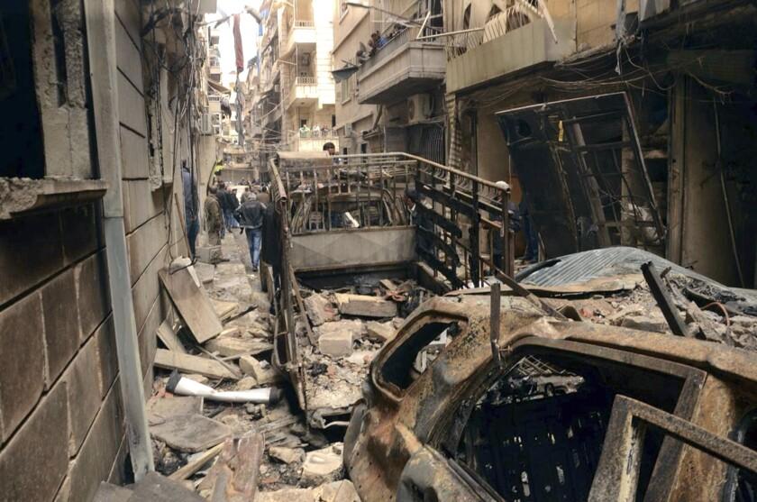 En imagen dada conocer por la agencia oficial de noticias siria SANA, un grupo de personas se reúne en una calle que fue alcanzada por fuego de artillería, en el vecindario predominantemente cristiano y armenio de Suleimaniye, en Alepo, Siria. (Foto AP/SANA)