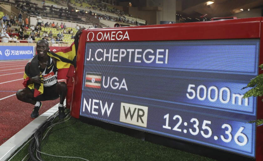 Uganda's Joshua Cheptegei poses next to the timing board after winning the men's 5000 meters race in a new world record time of 12:35.36 during the Diamond League athletics meeting at the Louis II stadium in Monaco Friday, Aug. 14, 2020.(Valery Hache /Pool Via AP)