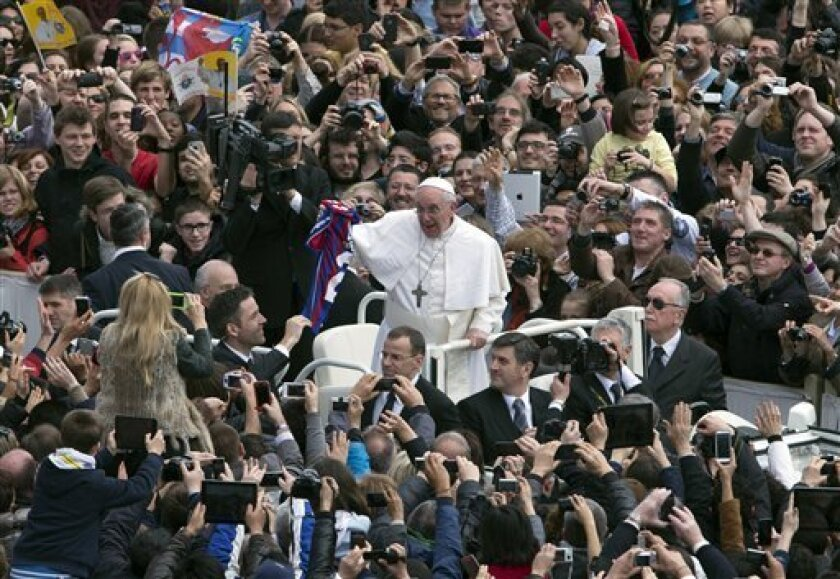 Pope Francis holds a San Lorenzo's soccer team jersey after celebrating his first Easter Mass in St. Peter's Square at the Vatican, Sunday, March 31, 2013. Pope Francis celebrated his first Easter Sunday Mass as pontiff in St. Peter's Square, packed by joyous pilgrims, tourists and Romans and bedec