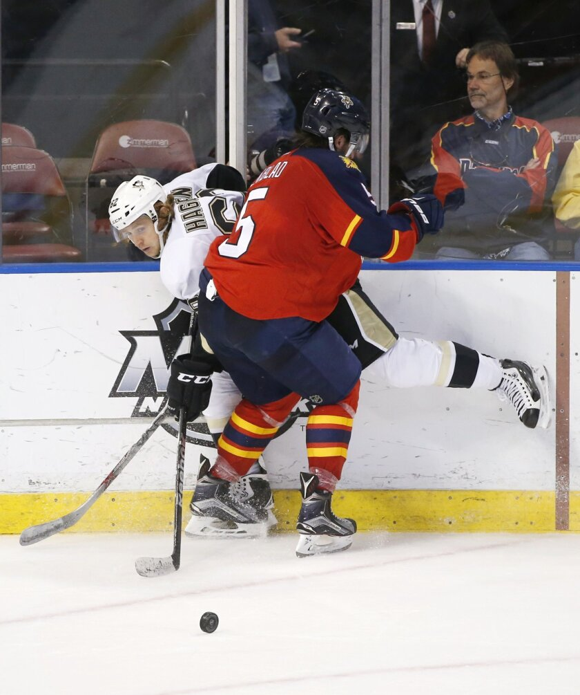Pittsburgh Penguins left wing Carl Hagelin (62) and Florida Panthers defenseman Aaron Ekblad (5) battle for the puck during the second period of an NHL hockey game, Monday, Feb. 15, 2016 in Sunrise, Fla. (AP Photo/Wilfredo Lee)