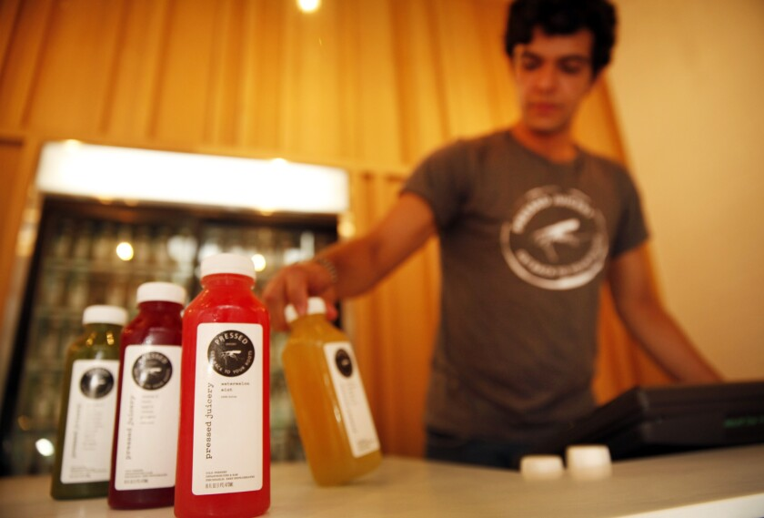 An employee at Pressed Juicery with a selection of juices from one of their refrigerated cases in the store.
