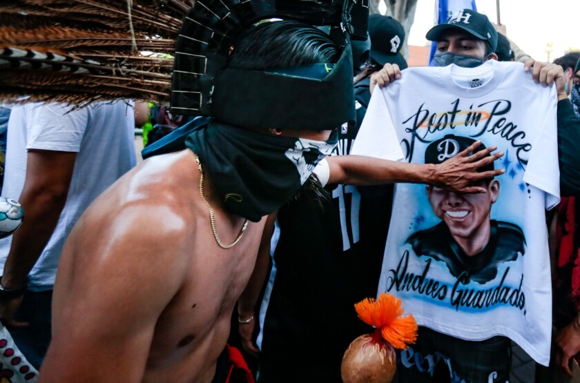 """A dancer in an Indigenous headdress touches a shirt reading """"Rest in Peace Andres Guardado"""" at a protest over his killing"""