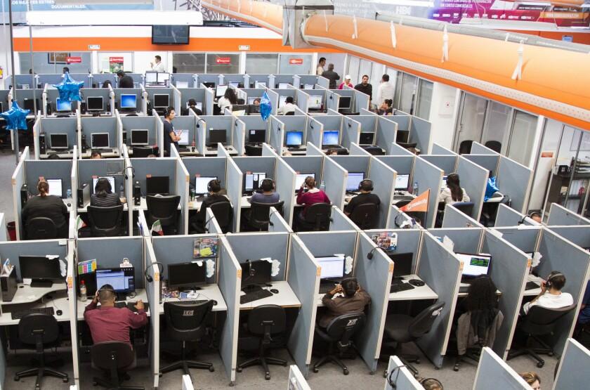 """En esta imagen del 13 de agosto de 2015, se ven trabajadores sentados en sus escritorios en un centro de atención telefónica en la ciudad fronteriza de Tijuana, México. Si uno pasa todo el día sentado, tal vez quiera programar una caminata energética, solo para asegurarse de tener al menos una hora de pie. Los científicos analizaron datos de más de un millón de personas y encontraron que se requiere al menos entre 60 y 75 minutos de ejercicios de """"intensidad moderada"""" para revertir el daño de pasar sentado al menos ocho horas al día. Encontraron que pasar sentado y no ejercitarse es tan dañino como la obesidad y el tabaquismo. (AP Foto/Alex Cossio, Archivo)"""