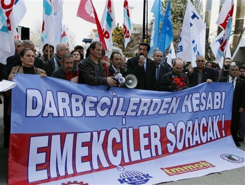 """Members of a leftist labor union stage a protest against the U.S. near the U.S. embassy in Ankara, Turkey, Tuesday, April 3, 2012. Demonstrators accused the U.S. of alleged support for the 1980 military coup in Turkey, a day before a trial begins against the coup leader Kenan Evren. The banner reads: """"The workers will bring the coup-makers to account!"""" (AP Photo)"""
