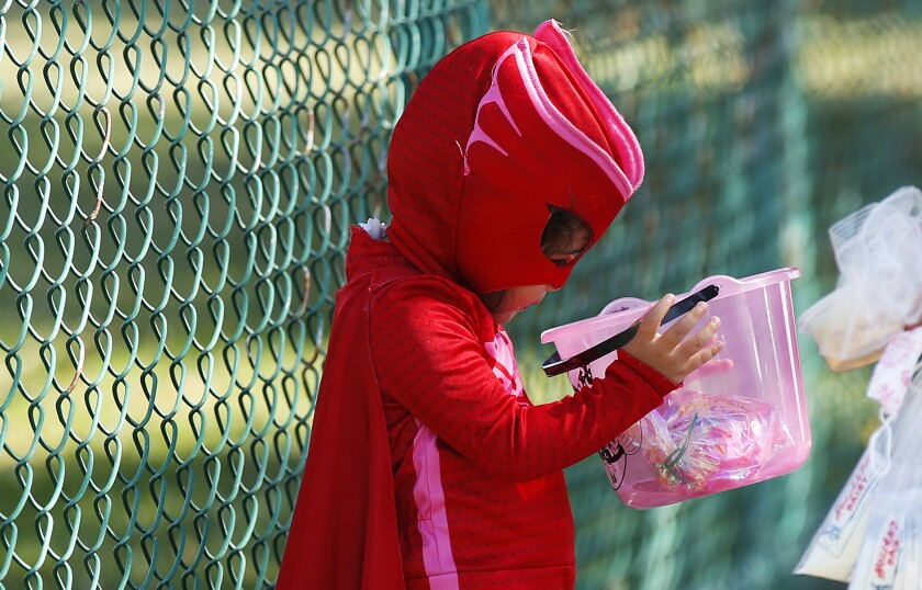 A child holds a bucket of candy at the City Heights Recreation Center in San Diego on Wednesday.