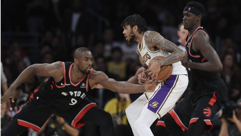Los Angeles Lakers' Brandon Ingram, center, is defended by Toronto Raptors' Serge Ibaka (9) and Pasc