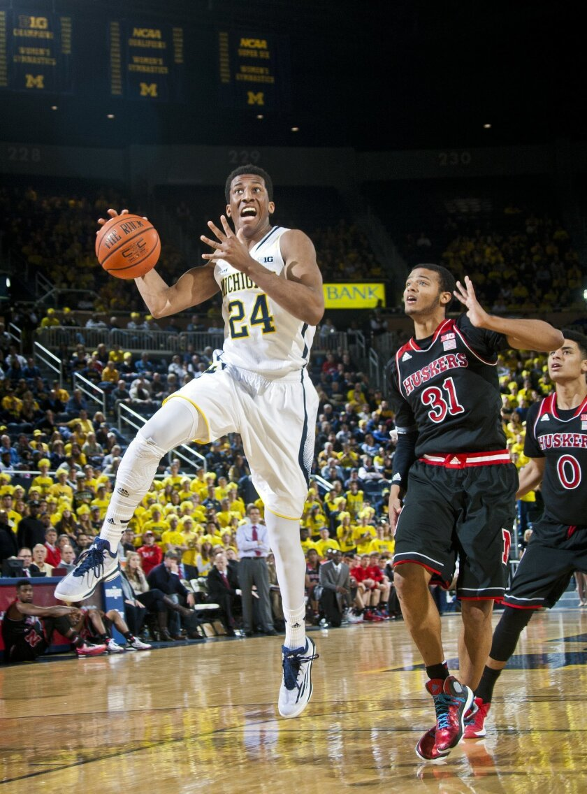 Michigan guard Aubrey Dawkins (24) goes to the basket, defended by Nebraska forward Shavon Shields (31), in the second half of an NCAA college basketball game at Crisler Center in Ann Arbor, Mich., Tuesday, Jan. 27, 2015. Michigan won 58-44. (AP Photo/Tony Ding)