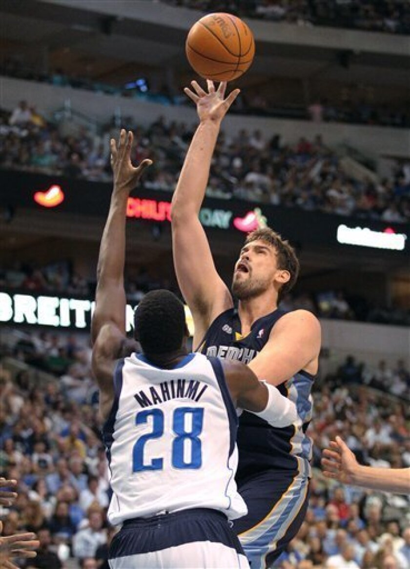 Memphis Grizzlies center Marc Gasol, right, goes for a shot against Dallas Mavericks center Ian Mahinmi during the first half of an NBA basketball game in Dallas on Wednesday, April 4, 2012. (AP Photo/Mike Fuentes)