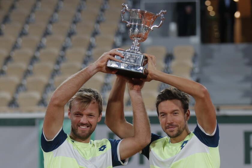 Kevin Krawietz, left, and Andreas Mies of Germany hold the trophy after winning the men's doubles final match of the French Open tennis tournament against Croatia's Mate Pavic and Brazil's Bruno Soares at the Roland Garros stadium in Paris, France, Saturday, Oct. 10, 2020. (AP Photo/Michel Euler)