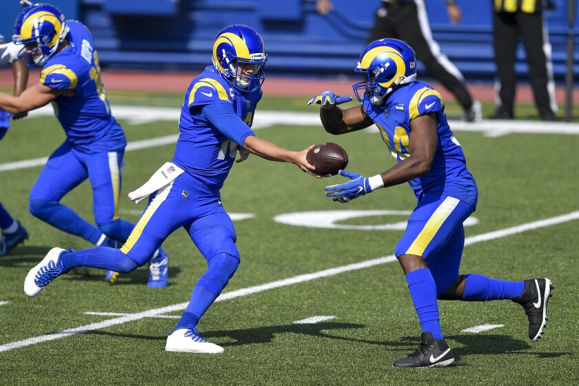 Rams quarterback Jared Goff hands the ball to running back Malcolm Brown.