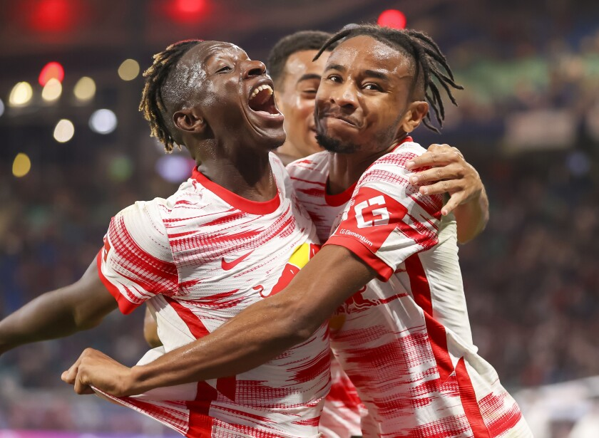 Leipzig's Christopher Nkunku, right, celebrates scoring with teammates Amadou Haidara, left, and Tyler Adams during the German Bundseliga soccer match between Leipzig and Vfl Bochum, at the Red Bull Arena in Leipzig, Germany, Saturday, Oct. 2, 2021. (Jan Woitas/dpa via AP)