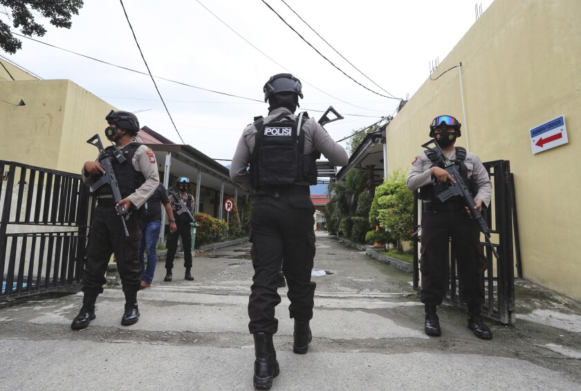 Police officers stand guard at a local police hospital where the bodies of militants killed during a raid were taken to, in Palu, Central Sulawesi, Indonesia, Sunday, July 11, 2021. Indonesian security forces say they have killed two suspected militants with ties to the Islamic State group and who are believed to be connected to the killing of Christian farmers. (AP Photo/Josua Marunduh)