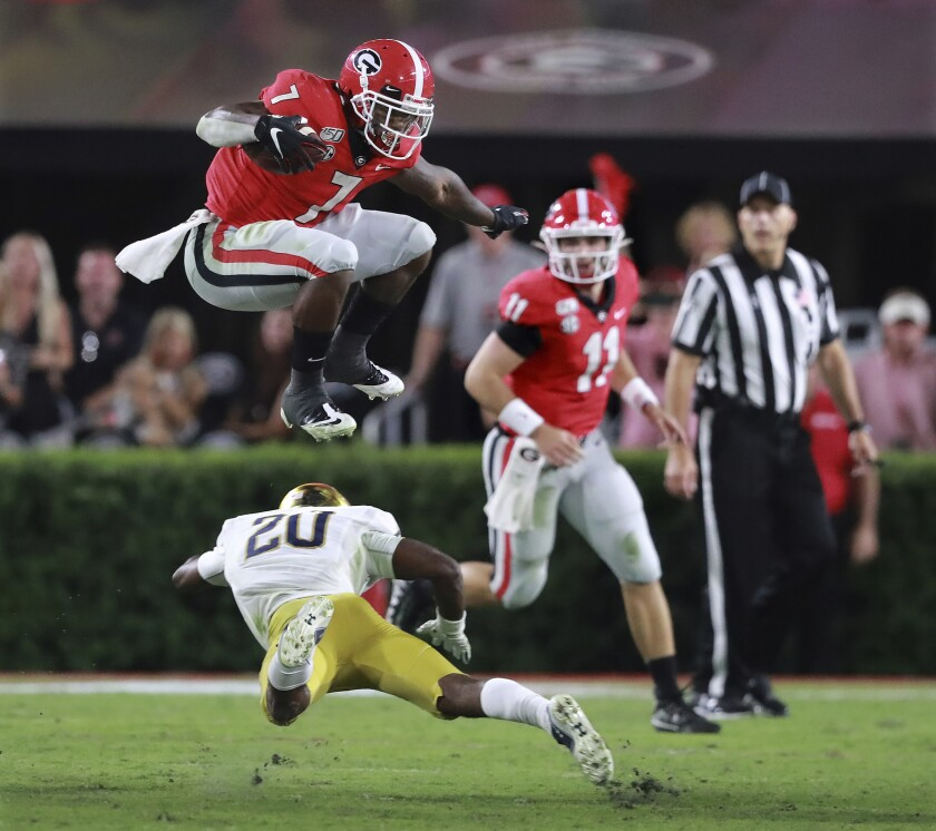 Georgia tailback D'Andre Swift leaps over Notre Dame cornerback Shaun Crawford with quarterback Jake Fromm watching, for a first down during the third quarter of an NCAA college football game Saturday, Sept. 21, 2019, in Athens, Ga. (Curtis Compton/Atlanta Journal Constitution via AP)