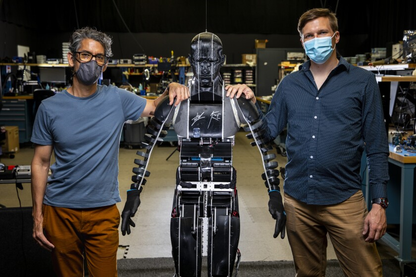 Two men resting their hands on the shoulders of a humanoid robot, center