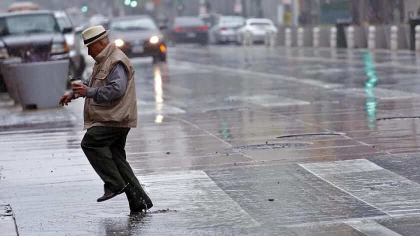 Un hombre brinca un charco de agua en la avenida Broadway, en Los Ángeles.