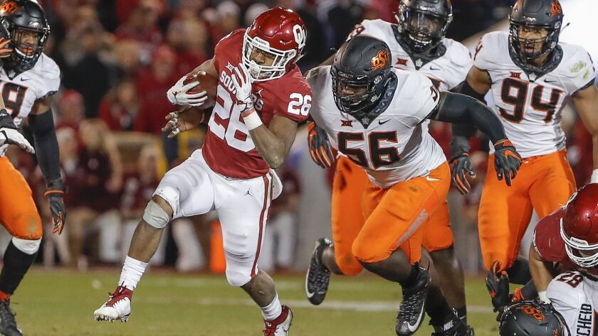 Oklahoma running back Kennedy Brooks (26) runs the ball ahead of Oklahoma State defensive tackle Eno