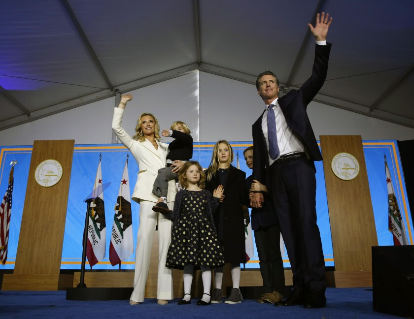"""FILE - In this Monday, Jan. 7, 2019 file photo, California Governor Gavin Newsom, right, his wife, Jennifer Siebel Newsom, left, and children wave after taking the oath office during his inauguration as 40th Governor of California in Sacramento, Calif. Two of Gov. Gavin Newsom's children have tested positive for the coronavirus and his office says the family is following """"all COVID protocols."""" A statement issued Friday, Sept. 17, 2021 says Newsom, his wife and two other children have since tested negative for the virus. (AP Photo/Rich Pedroncelli, File)"""