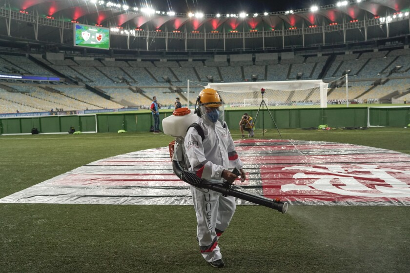 A worker wearing protective gear disinfects the pitch as a precaution against the coronavirus during the half break of the Rio de Janeiro soccer league final match between Flamengo and Fluminense at the Maracana stadium in Rio de Janeiro, Brazil, Wednesday, July 8, 2020. The match is being played without spectators to curb the spread of COVID-19. (AP Photo/Leo Correa)