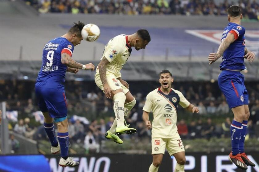 Cruz Azul's Milton Caraglio (L) fights for the ball with America's Victor Aguilera (C) during the Liga MX's Apertura tournament final on Dec. 16, 2018, at Azteca Stadium in Mexico City, Mexico. EPA-EFE FILE/Jose Mendez