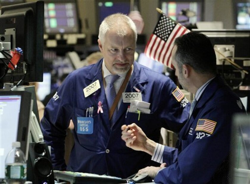 In this Nov. 1, 2010 photo, Thomas Bishop, left, talks with a fellow specialist on the floor of the New York Stock Exchange, Monday, Nov. 1, 2010. (AP Photo/Richard Drew)