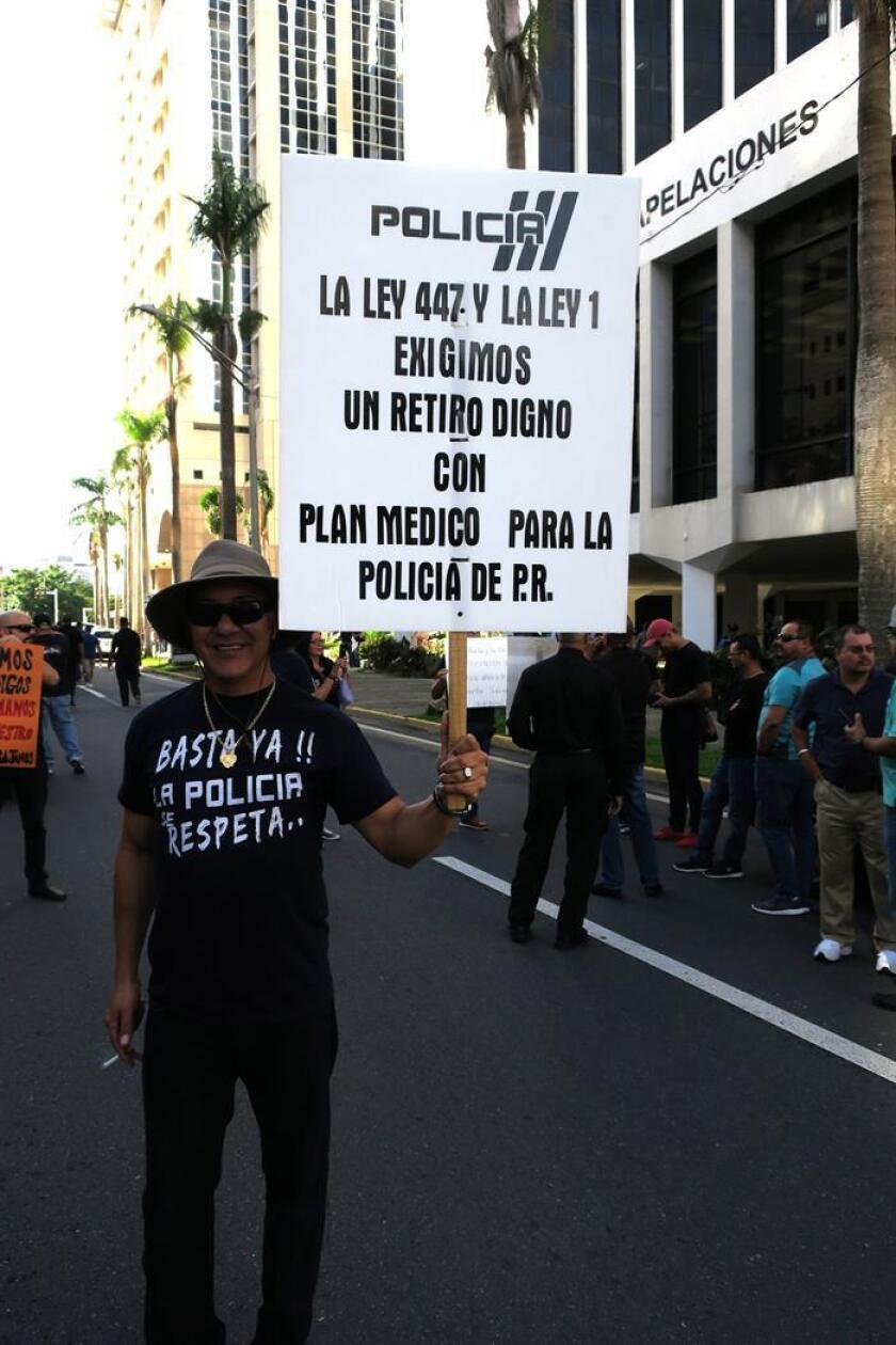 Un manifestante muestra un cartel durante una protesta de la Policía de Puerto Rico frente a las oficinas de la Junta de Supervisión Fiscal (JSF) en San Juan (Puerto Rico) para reclamar una jubilación digna y el pago de horas extras. EFE/Archivo