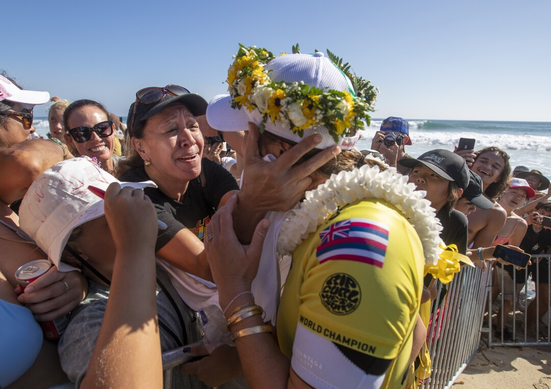 Carissa Moore gets a hug and lei from her mother, Carol Lum, after winning her fifth World Surf League Championship Title.