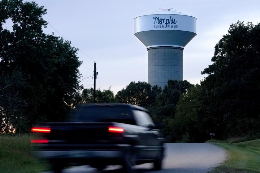 Una camioneta circula por una carretera rural cerca de un depósito de agua que señala la ubicación del Memphis Regional Megasite, el 24 de septiembre de 2021, en Stanton, Tennessee. (AP Foto/Mark Humphrey)