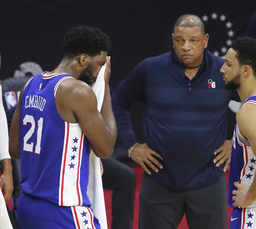 Philadelphia 76ers center Joel Embiid stands near coach Doc Rivers during the final seconds of the team's loss to the Atlanta Hawks in Game 5 of an NBA basketball Eastern Conference semifinal Wednesday, June 16, 2021, in Philadelphia. Embiid had missed two free throws. (Curtis Compton/Atlanta Journal-Constitution via AP)