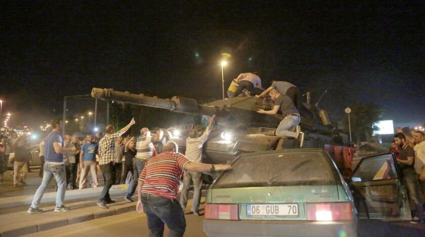 """Tanques avanzan hacia sus posiciones mientras civiles intentan detenerlos en Ankara, Turquía, la noche del viernes 15 de julio de 2016. La fuerzas armadas turcas dijeron el viernes que han """"tomado completo control"""" del país y el presidente exhortó a la ciudadanía a que salga a las calles en muestra de apoyo al gobierno. Una fuerte explosión se escuchó en la capital, Ankara, mientras jets caza sobrevolaban, disparos se escuchaban afuera de un cuartel militar y vehículos obstruían dos puentes importantes en Estambul.(AP Foto/Burhan Ozbilici)"""