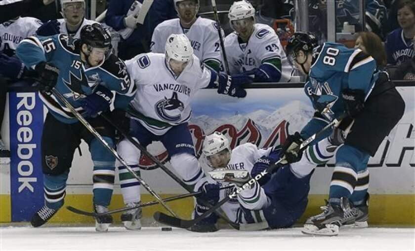 Vancouver Canucks right wing Jannik Hansen, from Denmark, bottom, looks for the puck in between defenseman Dan Hamhuis (2), San Jose Sharks center James Sheppard (15) and defenseman Matt Tennyson (80) during the second period of an NHL hockey game in San Jose, Calif., Monday, April 1, 2013. (AP Pho