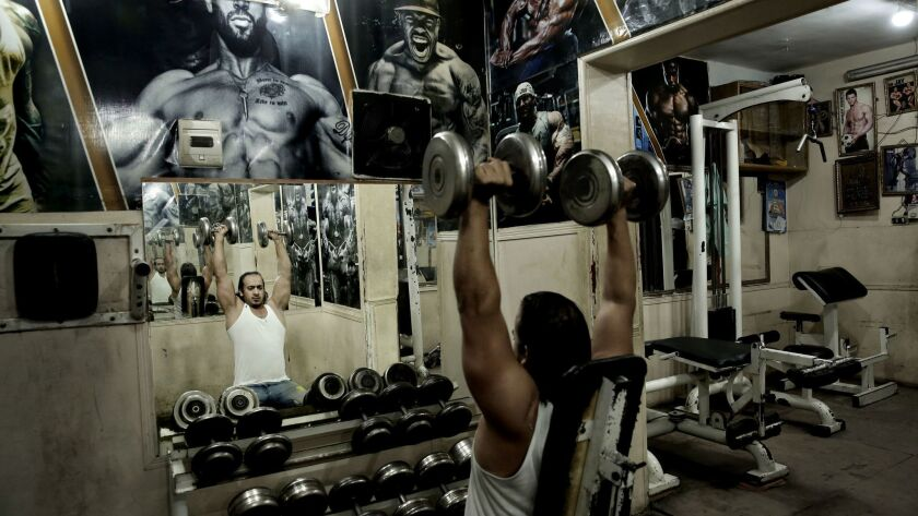 In this Oct. 23, 2018 photo, a man lifts barbells at a gym in the Shubra neighborhood of Cairo, Egyp