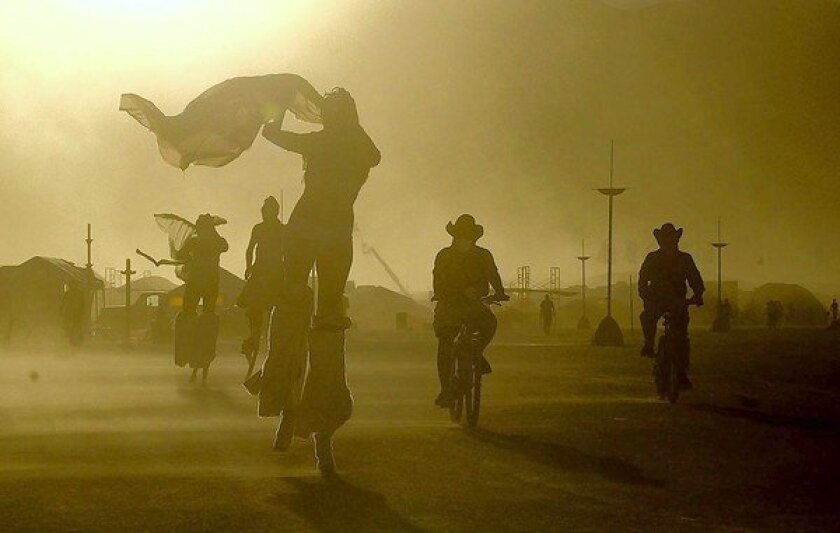A daylong windstorm whips sand at Burning Man in Black Rock Desert, Nev., as participants take evening bike rides and strolls on stilts in August 2005.