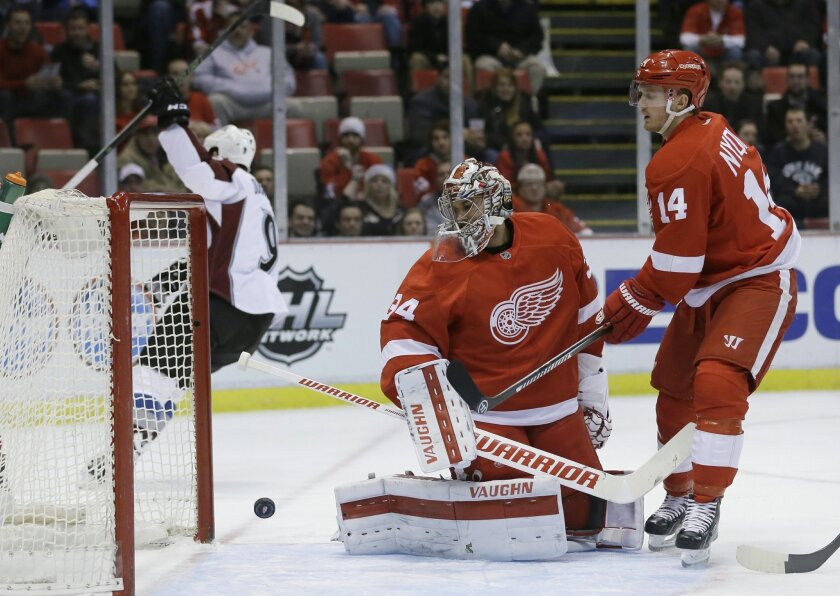 Detroit Red Wings goalie Petr Mrazek (34), of the Czech Republic, looks back with center Gustav Nyquist (14), of Sweden, as Colorado Avalanche center Matt Duchene scores during the first period of an NHL hockey game Friday, Feb. 12, 2016, in Detroit. (AP Photo/Carlos Osorio)