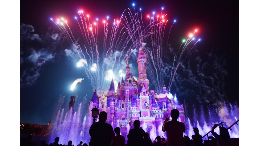Visitors watch fireworks explode over the castle at an event to mark the first anniversary of the opening of Shanghai Disneyland.